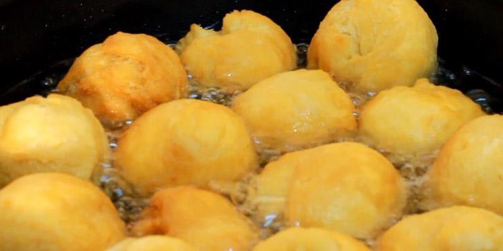 Chiên bánh bao trong chảo ngập dầu để nhân chín đều bên trong