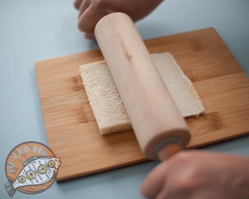 Cán dẹp phần bánh mì sandwich đã cắt bỏ các phần cạnh cứng